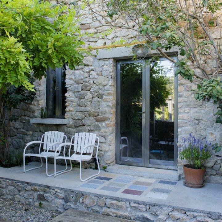 Twee witte stoelen op het terras bij de openslaande deuren