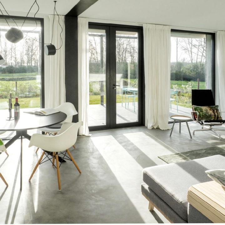 Lichte woonkamer met witte eetstoelen en betonnen vloer in een vakantiehuis