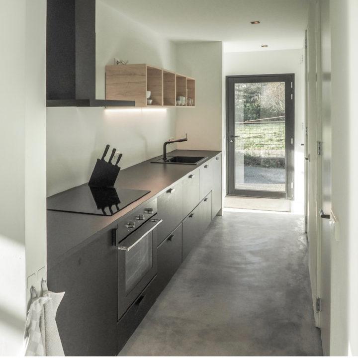 Zwarte keuken met betonnen vloer in een vakantiehuis