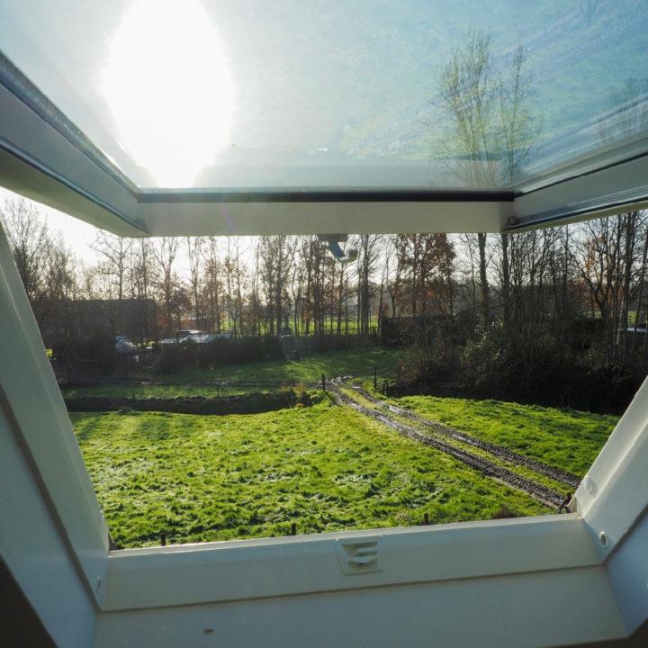 Uitzicht vanuit een dakraam over de tuin van een vakantiehuisje