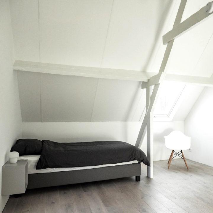 Witte slaapkamer met zwart bed in een vakantiehuisje