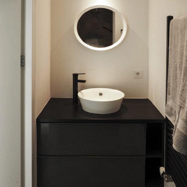Witte wastafel op zwart badmeubel in vakantiehuisje