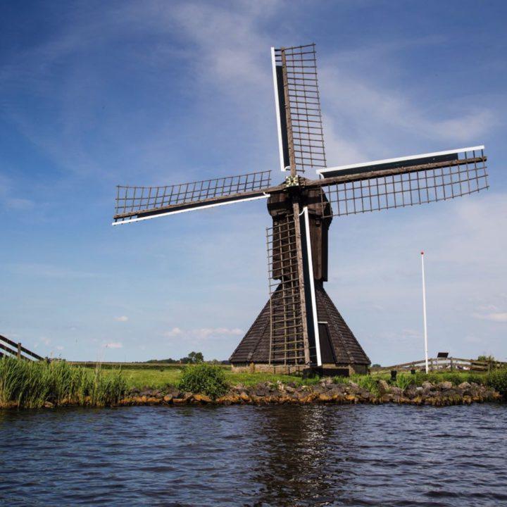 Zwarte molen aan de waterkant in Sandfirden