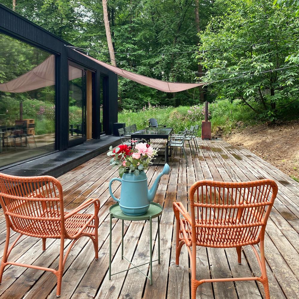 Terras met rode rotanstoelen en eettafel met 8 stoelen bij het vakantiehuis in het bos
