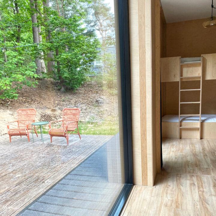 Vakantiehuis met grote ramen met terras buiten en slaapkamer binnen