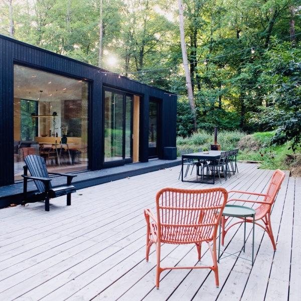 Zwart modern vakantiehuis met groot terras met rode rotan stoelen