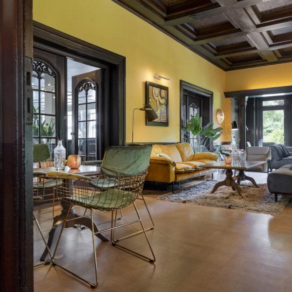De lounge met gele muren, gele banken en moderne stoelen in een hotel