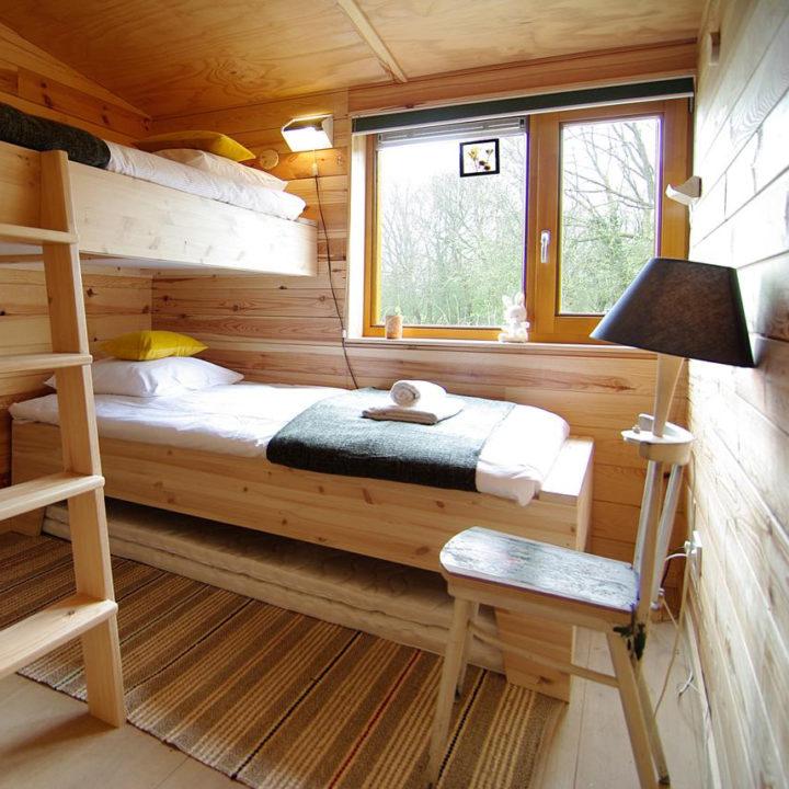 Een houten stapelbed in een houten slaapkamer in een lodge bij Amsterdam