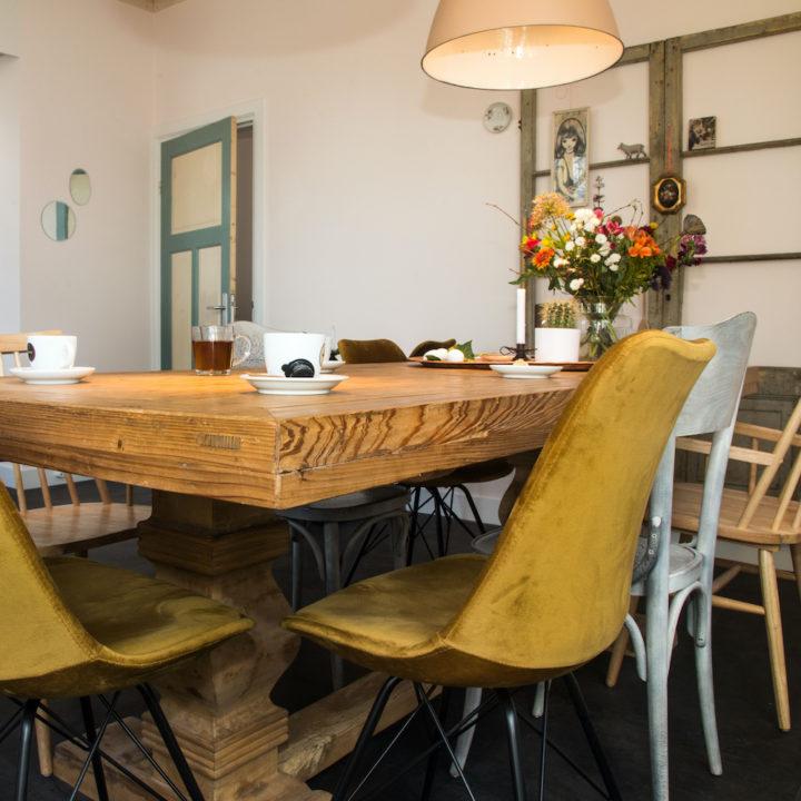 Eetkamer met verschillende stoelen rond de tafel