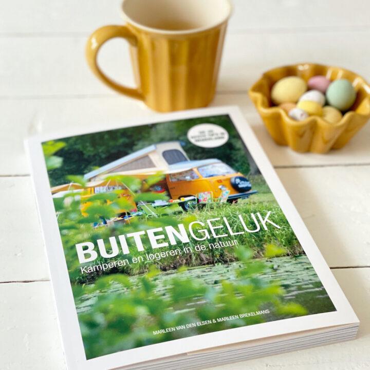 Boek buitengeluk naast een geel koffiekopje en geel schaaltje met paaseieren