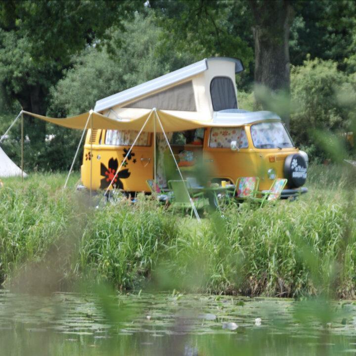 Gele Volkswagen T2 camper aan de waterkant