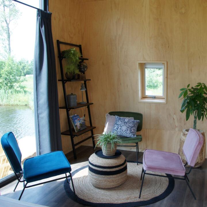 Zitje voor het raam, met planten, fauteuils en kussentjes