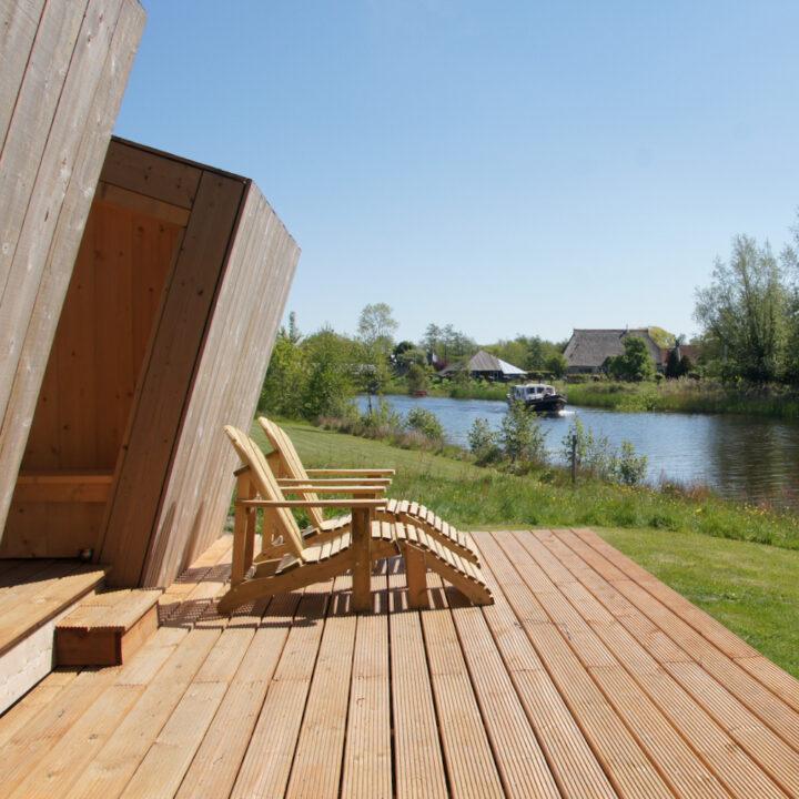 Huisje met twee ligstoelen aan het water