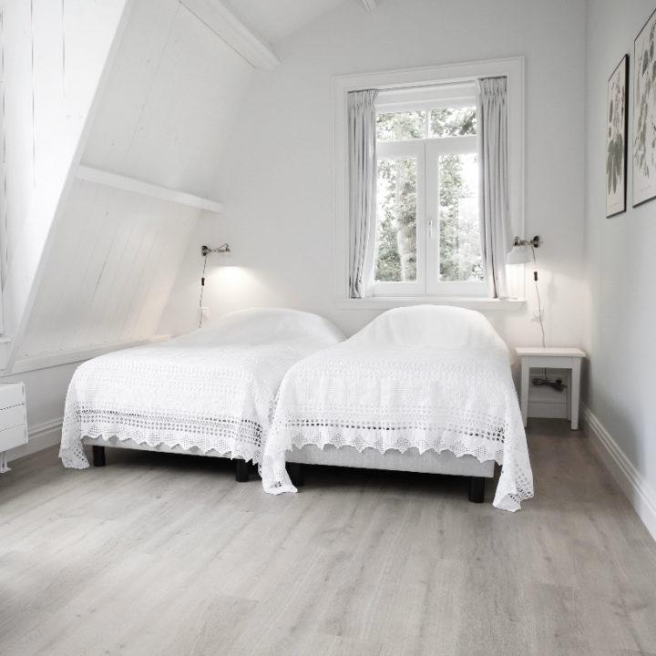 Witte opgemaakte bedden in een appartement, voor een vakantie aan zee