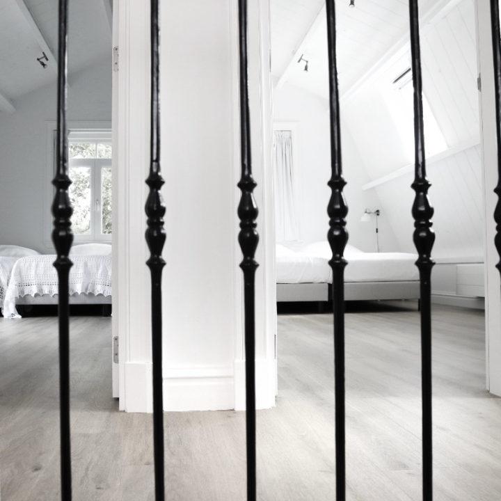 Overloop met zwart hekje in een vakantie appartement