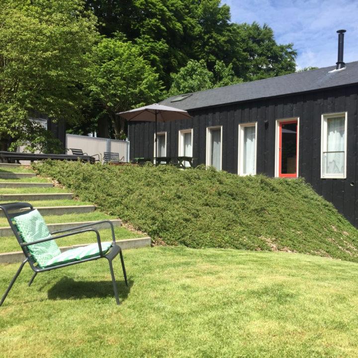 Tuinstoel op een grasveld met op de achtergrond een vakantiehuis.