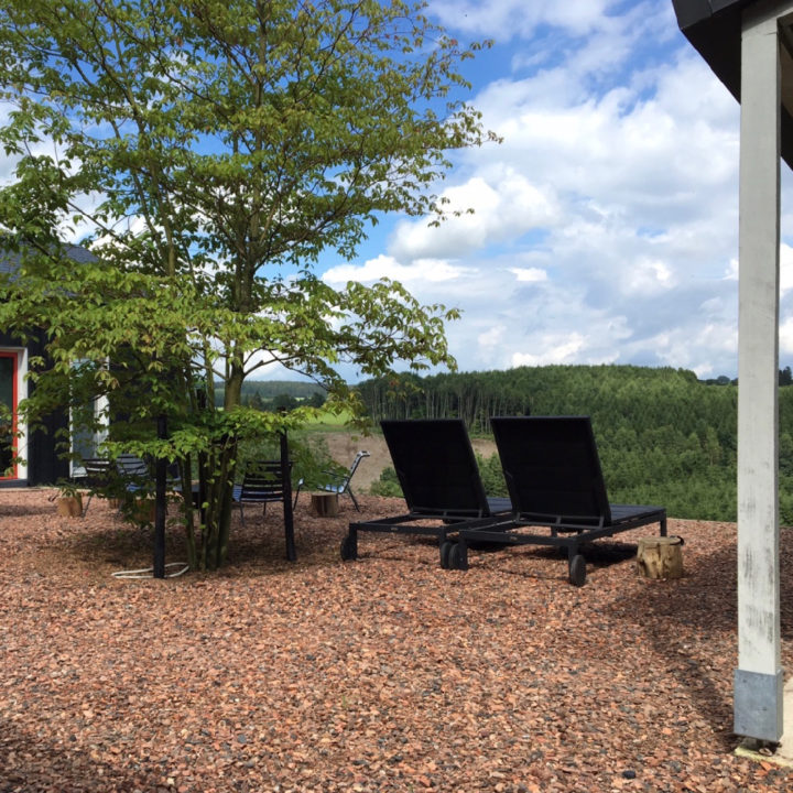 Tuin met terras en ligbedden bij een vakantiehuis in de ardennen
