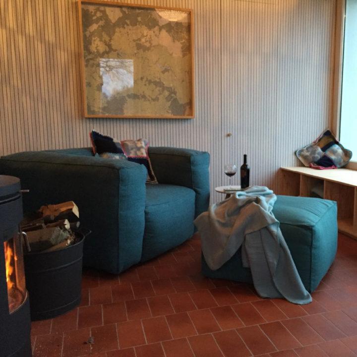 Een groene luie stoel met poef bij een brandende kachel in een vakantiehuis in de Ardennen