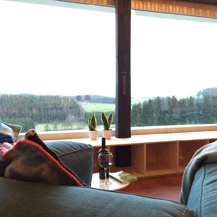 Woonkamer in een vakantiehuisje in de Ardennen, met grote ramen en mooi uitzicht