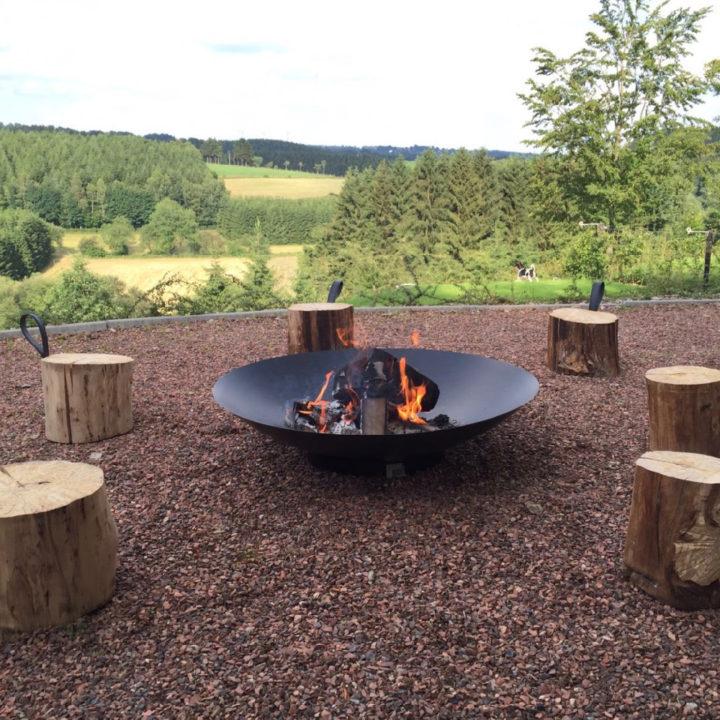 Een vuurschaal met houten krukjes eromheen