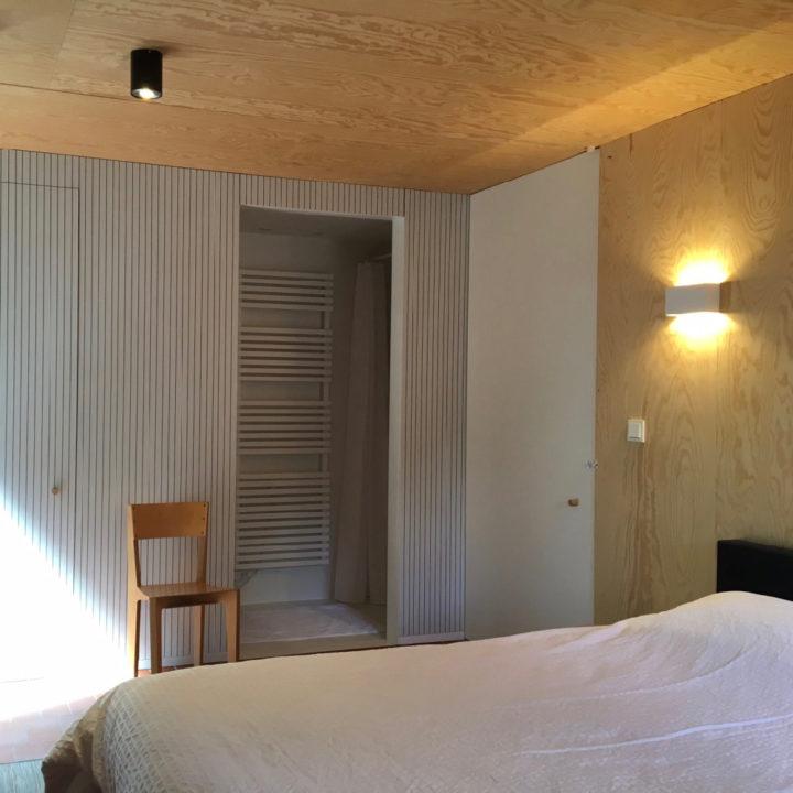 Een slaapkamer met een bed, stoel en deur naar de ensuite badkamer