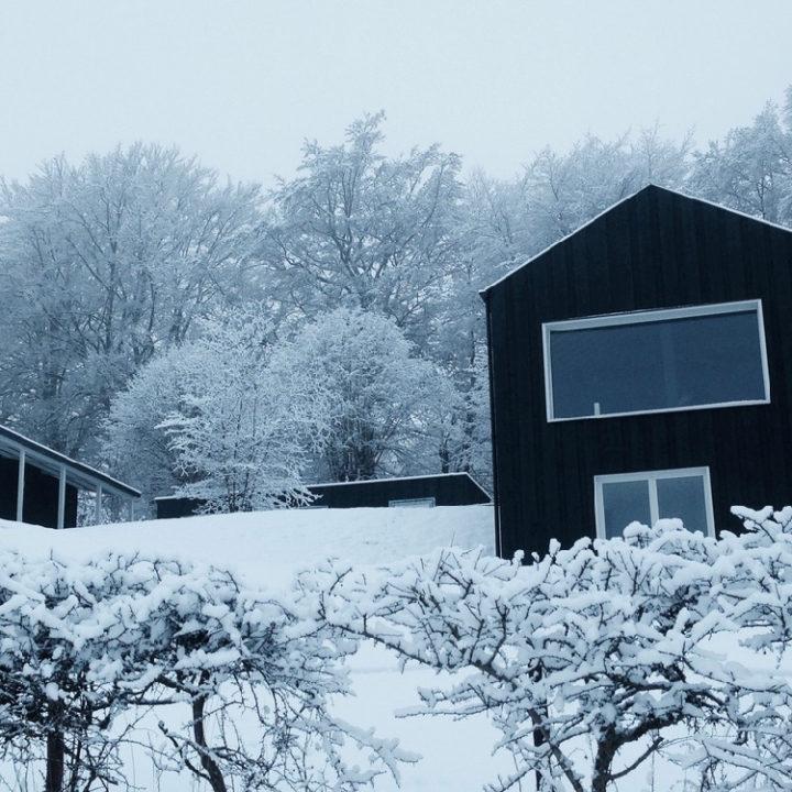 Een zwart vakantiehuisje in de sneeuw in de Ardennen