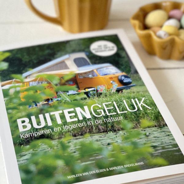 Boek op tafel, met de titel Buitengeluk. Een geel Volkswagenbusje op de cover