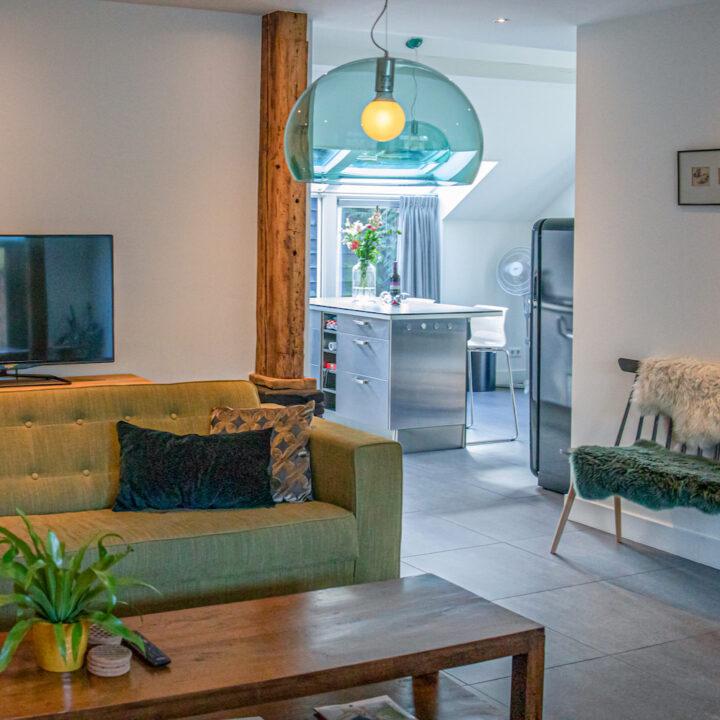Groene zitbank met erachter een glimp van de moderne keuken
