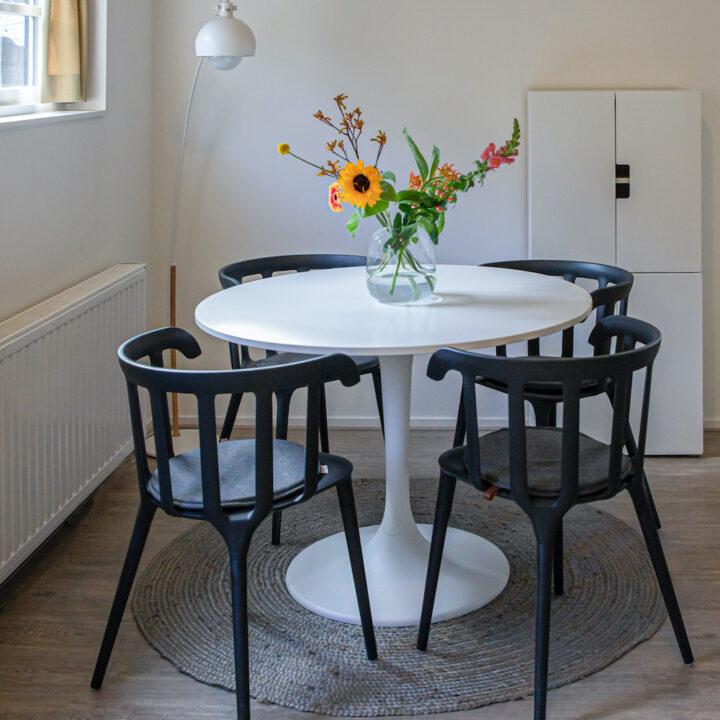 Witte ronde eettafel met zwarte stoeltjes