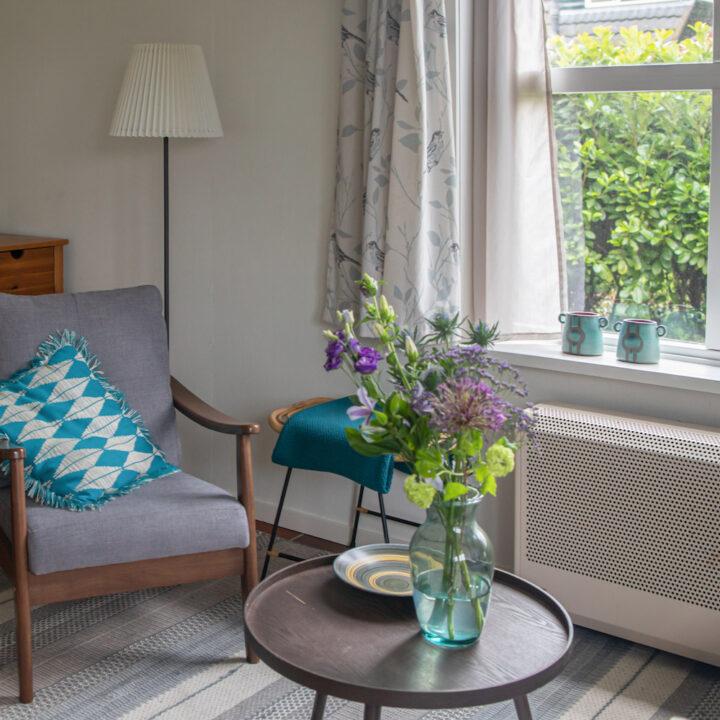 Zithoek in het vakantiehuis met fauteuil en bos bloemen