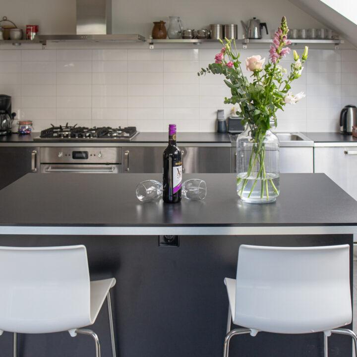 Strakke moderne keuken met wijn en bloemen op tafel