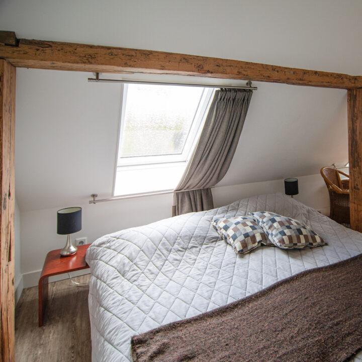 Tweepersoons bed onder een schuin dak met stoere gebinten
