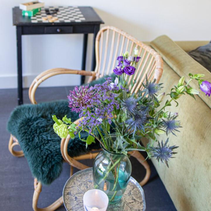 Bos bloemen op een tafeltje naast een rotan stoel