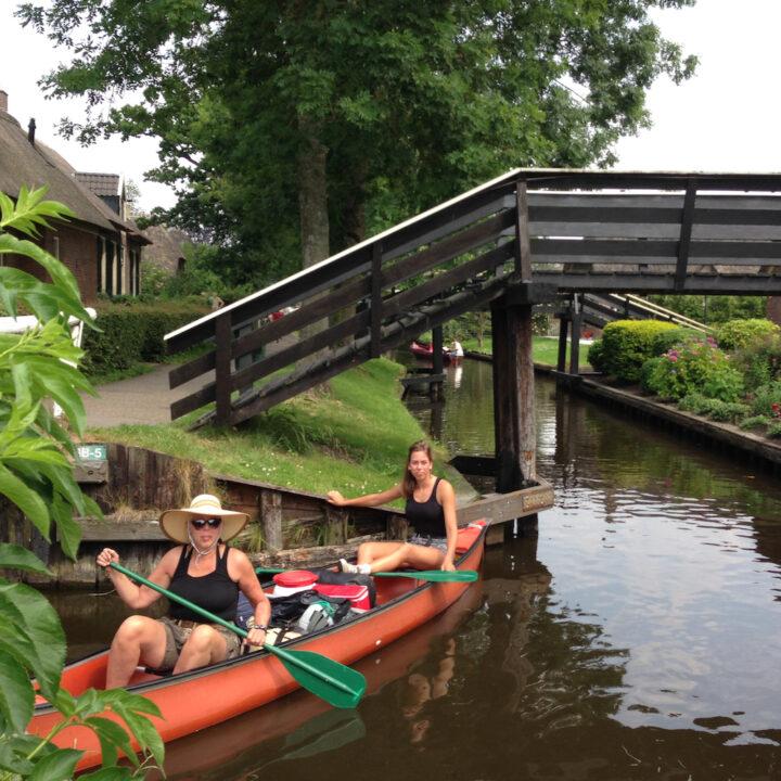 Een stel vriendinnen vaart met een kano door Giethoorn