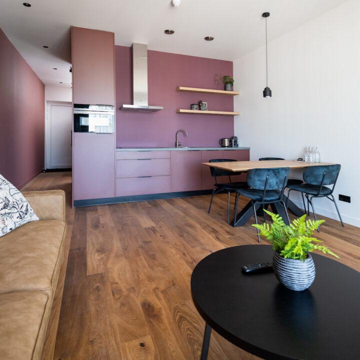 Studio met zithoek, eethoek en roze keuken