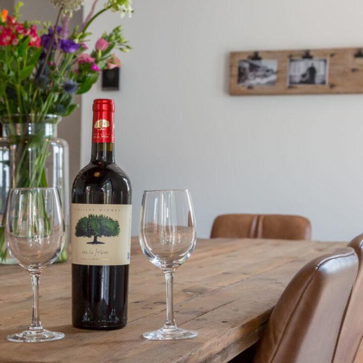 Fles wijn op tafel als welkom in het vakantiehuis Zeeland