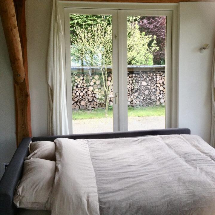 Slaapkamer met tuindeuren in het natuurhuisje in Haaren