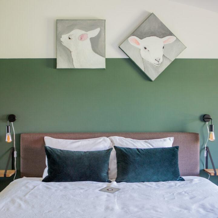 Kamer met schaapjes schilderijen boven het bed