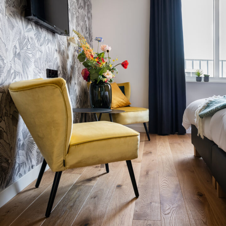 Gele fauteuils met bos bloemen op hotelkamer in Hotel de Beerze in Brabant