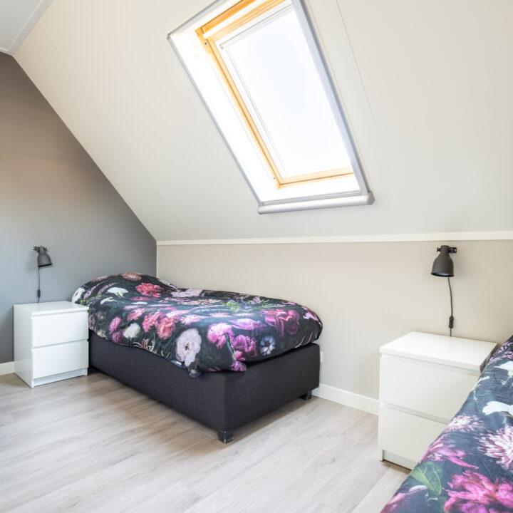 Slaapkamer met twee bedden in appartement op Ameland