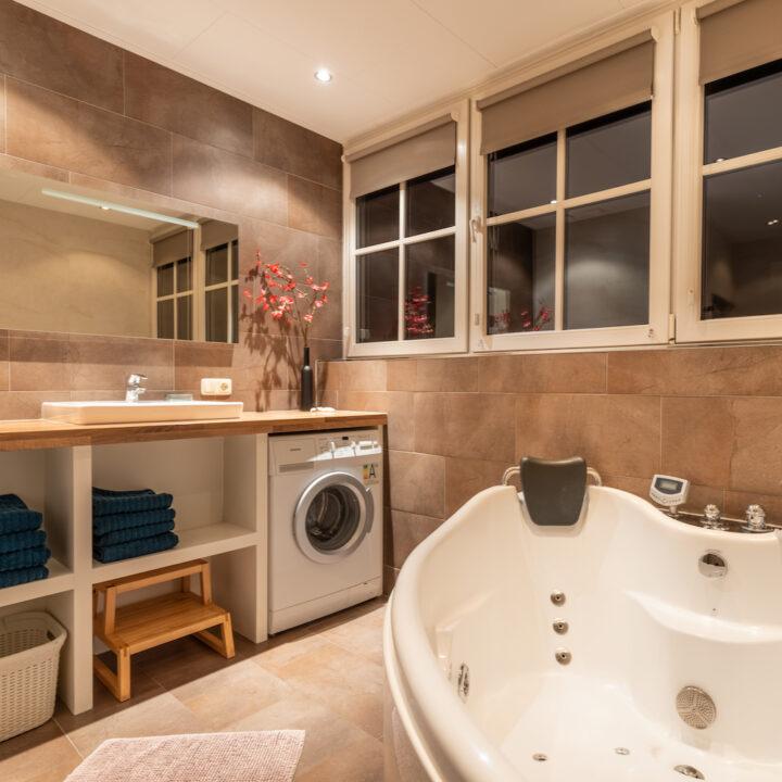 Badkamer met tweepersoons bad in het vakantiehuis op Ameland