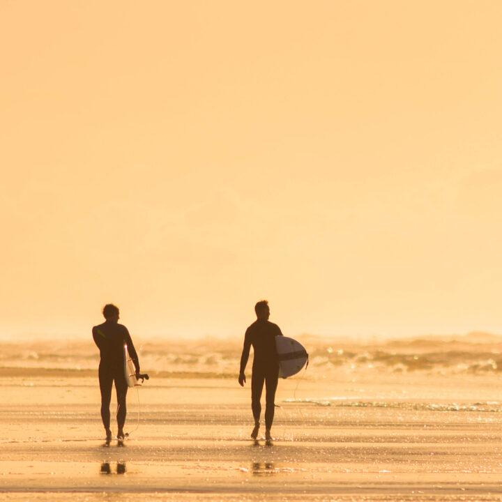 Twee surfers op Ameland in het avondlicht
