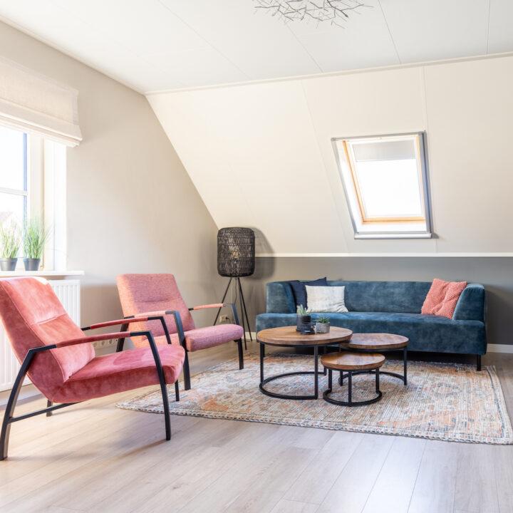 Twee roze fauteuils en grijsblauwe bank in de zithoek van het appartement voor een vakantie op Ameland