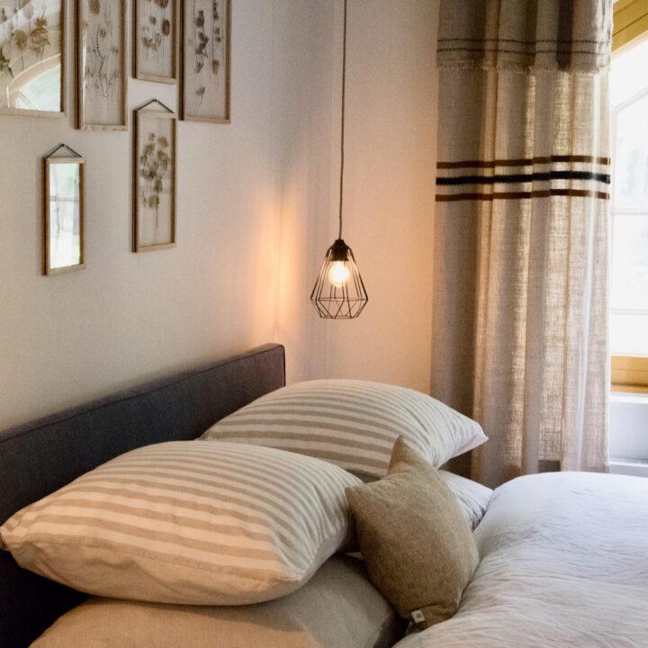 Slaapkamer met zicht op de tuin en leuke schilderijen boven het bed