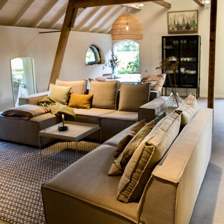 Ruime woonkamer met grote hoekbank in het vakantiehuis in Linschoten