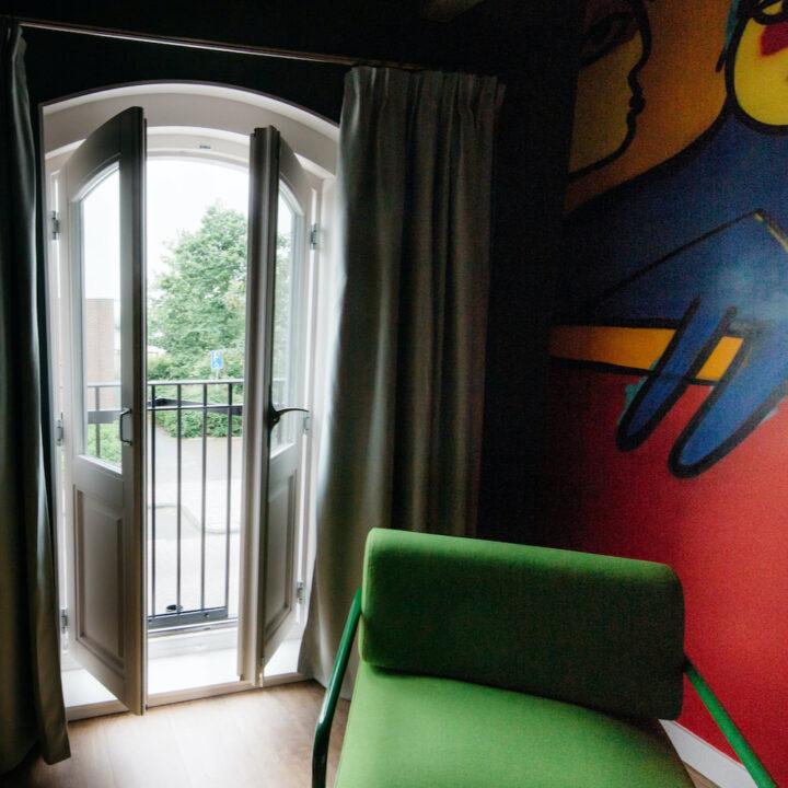 Hotelkamer met felle kleuren op de muur