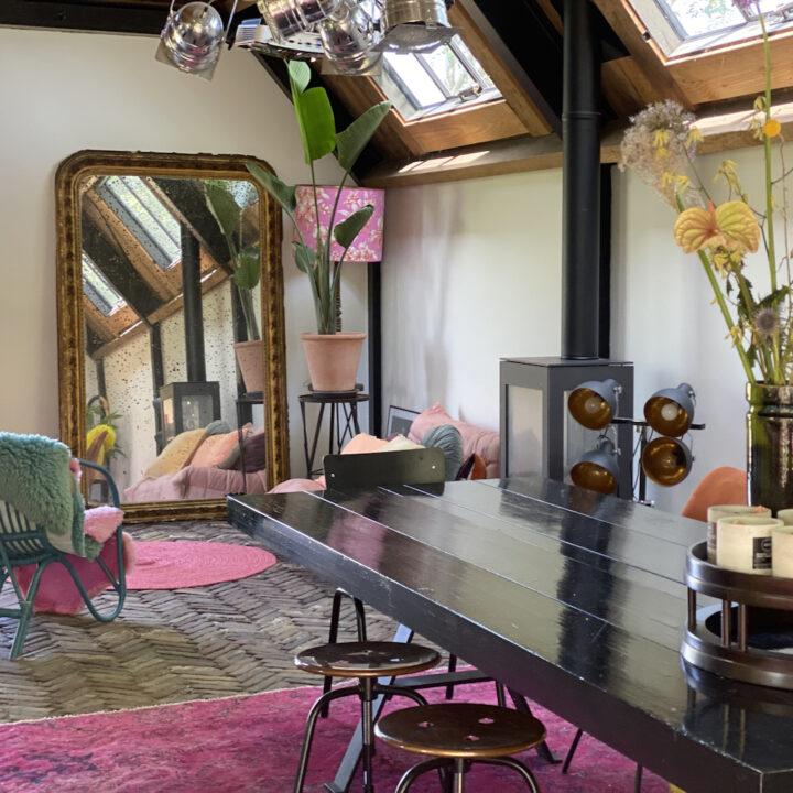 Woonkamer met diverse stoelen, een roze kleed, bloemen