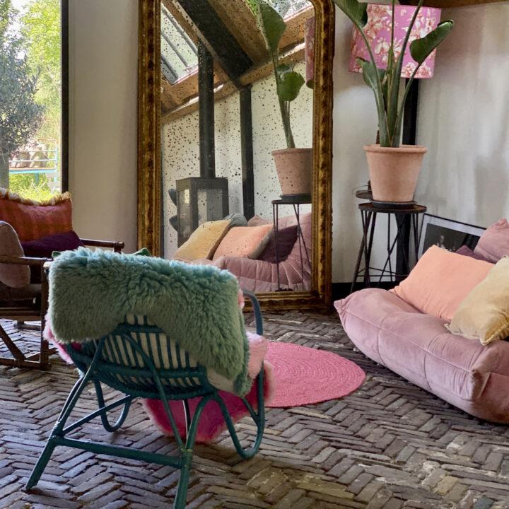 Zithoek in de B&B met roze bank en groene rotan stoel met schapenvacht