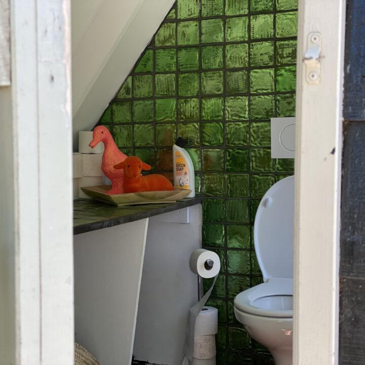 Toilet met groene tegelwand bij de B&B