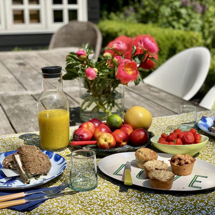 Gedekte tafel met taartjes, boterhammen, sap en fruit